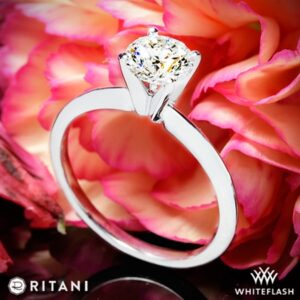a four prong solitaire with a diamond photographed with a pink flower